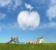 Couples menteur sur le collage de pomme d'herbe et de rêve Photographie stock
