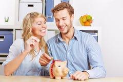 Couples mettant d'euro pièces de monnaie d'argent Photo stock