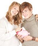 Couples mettant l'euro cinq à la tirelire Photographie stock