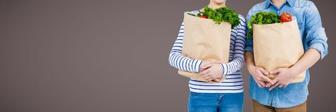 Couples mid sections with grocery bags against brown background Stock Photos