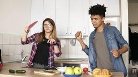 Couples mignons étant idiots, dansant dans la cuisine avec la batterie de cuisine Fille caucasienne attirante et son ami de mulât clips vidéos