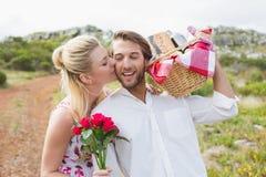 Couples mignons allant pour un pique-nique avec la joue de baiser d'amis de femme Images libres de droits