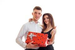Couples mignons avec du charme se tenant près du sourire et de porter un grand boîte-cadeau rouge Images stock