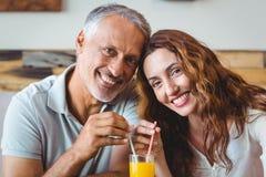 couples mignons ayant le verre de jus d'orange Images libres de droits