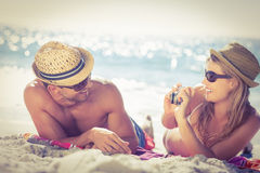 Couples mignons clouant des photos sur la plage images stock