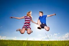 Couples mignons d'amusement dans le saut sur le fond extérieur Photo libre de droits