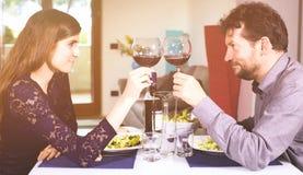 Couples mignons dans l'amour se regardant dans les yeux grillant et célébrant Photos libres de droits
