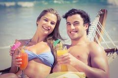 Couples mignons dans l'hamac buvant un cocktail Image stock