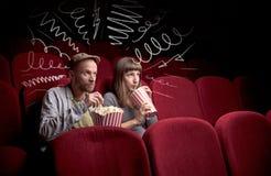 Couples mignons dans le film de observation de cinéma Image stock