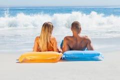 Couples mignons dans le maillot de bain prenant un bain de soleil ensemble Images libres de droits