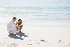 Couples mignons dessinant un coeur dans le sable Photo stock