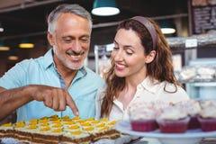 Couples mignons dirigeant des pâtisseries Photographie stock libre de droits