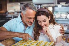 Couples mignons dirigeant des pâtisseries Photos libres de droits