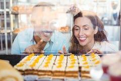 Couples mignons dirigeant des pâtisseries par le verre Photographie stock