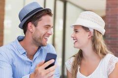 Couples mignons discutant au-dessus du smartphone Image stock