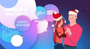 Couples mignons en bulles de Santa Hats Embracing Over Chat avec des vacances d'hiver de messages de Joyeux Noël et de bonne anné Photographie stock libre de droits