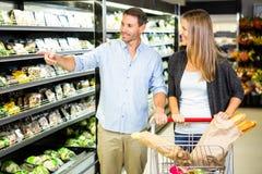 Couples mignons faisant l'épicerie ensemble Photographie stock