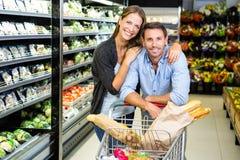 Couples mignons faisant l'épicerie ensemble Image stock