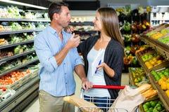 Couples mignons faisant l'épicerie ensemble Photo stock