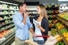 Couples mignons faisant l'épicerie ensemble Photos stock