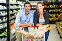 Couples mignons faisant l'épicerie ensemble Image libre de droits