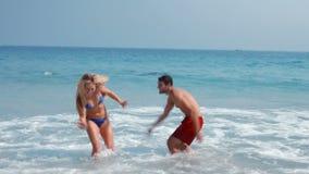 Couples mignons heureux ayant l'amusement à la plage clips vidéos