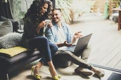 Couples mignons heureux dans l'amour avec du café et le smili potables d'ordinateur portable Images stock