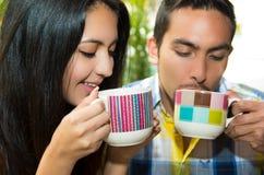 Couples mignons hispaniques appréciant le café pendant un confortable Images libres de droits