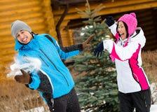 Couples mignons jouant aux boules de neige et ayant l'amusement Photos stock