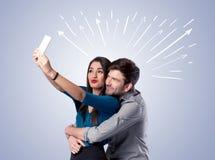 Couples mignons prenant le selfie avec des flèches Photos libres de droits