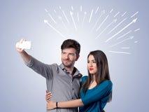 Couples mignons prenant le selfie avec des flèches Photographie stock