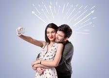 Couples mignons prenant le selfie avec des flèches Image libre de droits