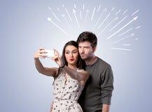 Couples mignons prenant le selfie avec des flèches Image stock
