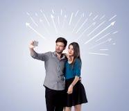 Couples mignons prenant le selfie avec des flèches Photographie stock libre de droits
