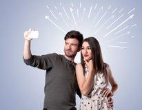 Couples mignons prenant le selfie avec des flèches Images stock