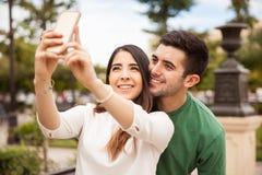 Couples mignons prenant un selfie dehors Images libres de droits