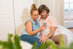Couples mignons regardant l'écran de smartphone Photos libres de droits