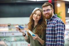 Couples mignons regardant l'appareil-photo avec des produits dans le supermarché images stock