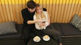 Couples mignons regardant un smartphone un café Photos stock