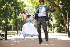 Couples mignons sautant et souriant sur le parc de fond Images libres de droits