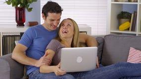 Couples mignons se reposant dans le salon avec l'ordinateur portable photographie stock