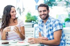 Couples mignons se reposant dehors à un café avec l'homme souriant à l'appareil-photo photographie stock libre de droits