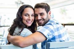 Couples mignons se reposant en dehors d'un café souriant à l'appareil-photo Photographie stock libre de droits