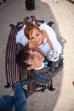 Couples mignons se reposant sur le banc et souriant sur le fond Lviv Images stock
