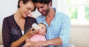 Couples mignons se reposant sur un sofa et allaitant au biberon à leur bébé banque de vidéos