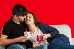Couples mignons sur le café potable de divan. Photo stock