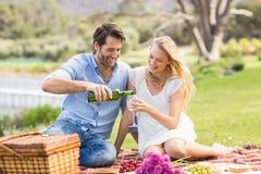 Couples mignons sur le vin de versement de date dans un verre Photographie stock