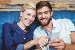 Couples mignons sur les photos de observation d'une date sur un smartphone Images stock