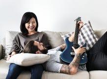 Couples mignons sur un ami de divan jouant une musique de guitare et un concept d'amour Image libre de droits