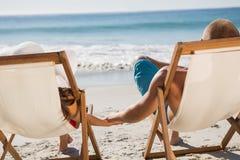 Couples mignons tenant des mains tout en se trouvant sur leurs chaises de plate-forme Photos stock
